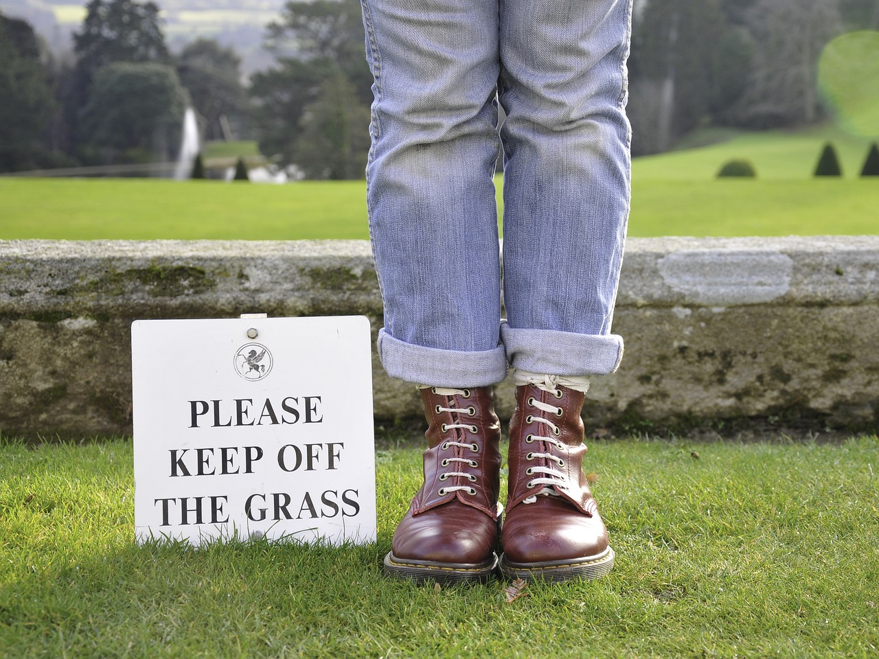 "Man Standing on Grass next to ""Please Keep Off the Grass"" Sign"