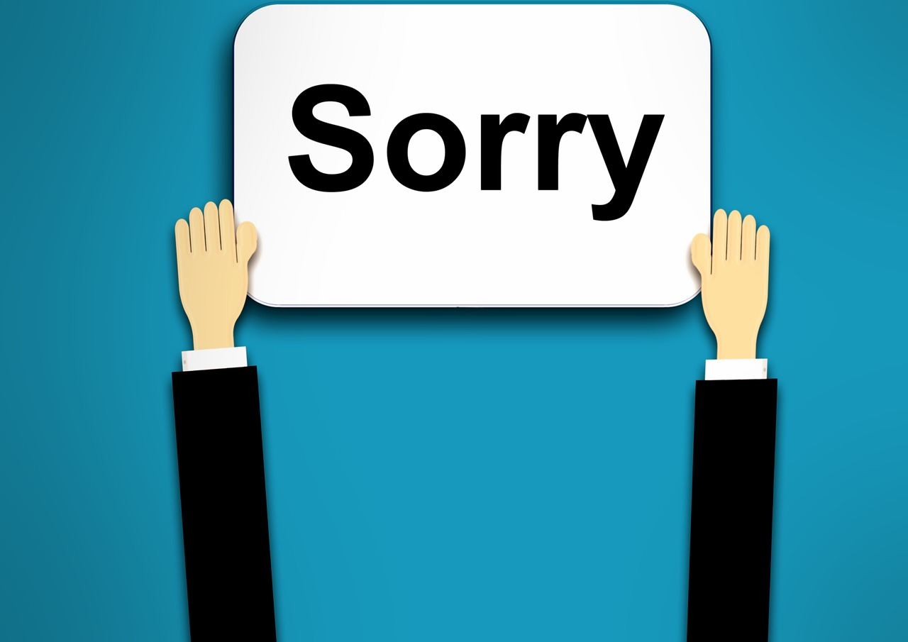Businessperson Holding Up Sorry Sign